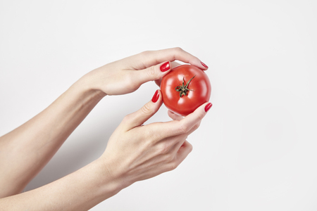 Fresh vegetable tomato in womans hands, fingers with red nails manicure, isolated on white background, healthy lifestyle concept