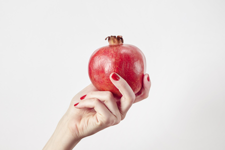Red fresh pomegranate in womans hand isolated on white. Vegetables and fruits summer concept