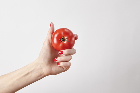 Fresh vegetable tomato in woman hand, fingers with red nails manicure, isolated on white background, healthy lifestyle concept Banque d'images