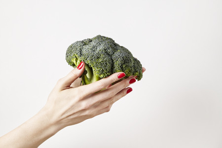 Fresh vegetable broccoli in woman outstretched hand, fingers with red nails manicure, isolated on white background, healthy lifestyle concept Stock Photo