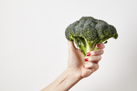 Fresh vegetable broccoli in woman hand, fingers with red nails manicure, isolated on white background, healthy lifestyle concept
