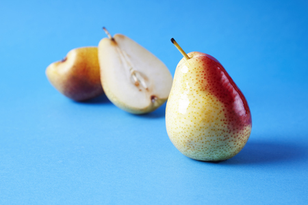 Whole fresh ripe pears fruits on blue background, modern style food picture, summer wallpaper design Banque d'images