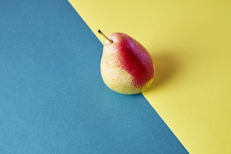 Whole fresh ripe pear, fruit view from above on blue yellow background, modern style food picture, wallpaper design Stock Photo