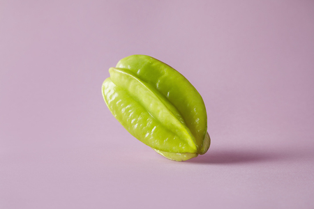 Fresh green tropical carambola on pink background. Hipster vegetables and exotic fruits for layout, healthy concept