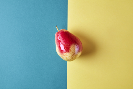 Whole fresh pear fruit view from above on green yellow background, modern style food picture, pattern design Stock Photo