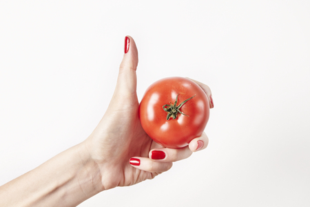 Fresh vegetable tomato in woman hand, fingers with red nails manicure, isolated on white background, healthy lifestyle concept Stock Photo