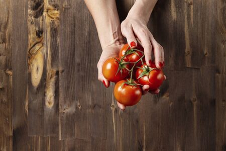 Fresh red tomatoes in womans hands with beautiful fingers, wooden background, vegetarian farm products concept