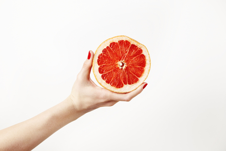 Juicy fresh grapefruit in a beautiful womans hand isolated on white Stock Photo