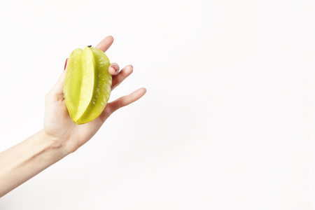 Fresh green tropical carambola in woman hand with red nails, isolated on white background. Hipster style vegetables fruits for layout, healthy concept