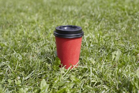 Red paper cup of coffee to takeaway on green grass lawn. Breakfast morning outside the cafe Stock Photo