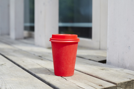 Red paper cup of coffee to takeaway on wooden floor outside the cafe. Breakfast morning on air Banque d'images