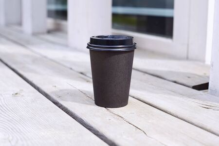 black paper cup of coffee to takeaway on wooden floor outside the cafe. Breakfast morning on air Stock Photo