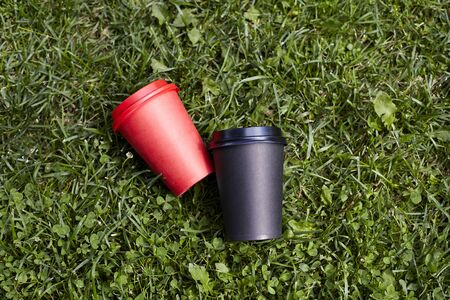 Two paper cups with coffee to take away, red and  black cup on green grass outdoor breakfast Stock Photo