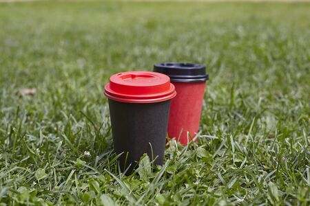 Black and red paper cups of coffee to takeaway on green grass lawn. Breakfast morning outside the cafe Stock Photo