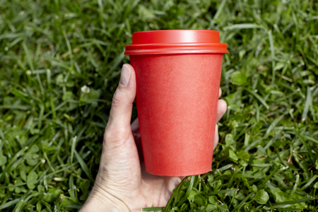Red paper cup of coffee to takeaway on green grass lawn in woman hand. Breakfast morning outside the cafe Stock Photo