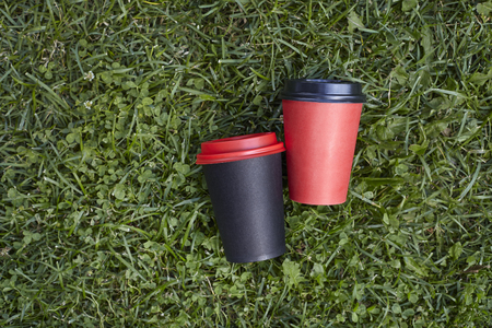 Two paper cups with coffee to take away, red and  black cup on green grass outdoor breakfast Banque d'images