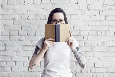 Pretty donna tatuata hipster pone in maglietta bianca con il libro in mani, isolato su bianco muro di mattoni, Tenere un libro in mano, spazio per la progettazione layout