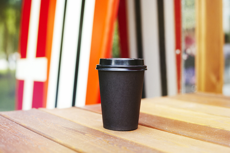 Black paper cup of coffee to takeaway on wooden floor outside the cafe. Surfing boards stand behind at the background Stock Photo