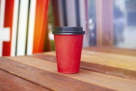 Red paper cup to takeaway on wooden floor outside the cafe. Surfing boards stand behind at the background Stock Photo