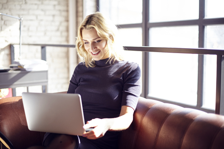 portative: Beautiful blonde businesswoman sitting in sunny office working on laptop. Concept of young people working mobile devices. Sunshine throw windows on background Stock Photo