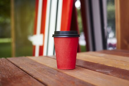 Red paper cup to takeaway on wooden floor outside the cafe. Surfing boards stand behind at the background Banque d'images
