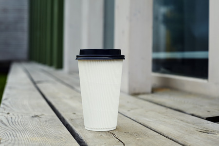 ripple: Ripple white paper cup of coffee to takeaway at the wooden floor terrace outside