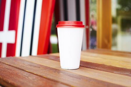 Ripple white paper cup to takeaway on wooden floor outside the cafe. Surfing boards stand behind at the background Stock Photo