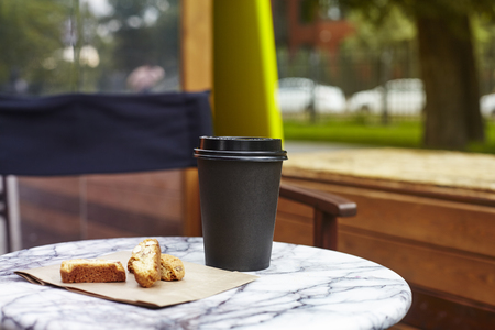 black paper disposable cup of coffee to takeaway on marble table in garden outside cafe. Breakfast morning on air
