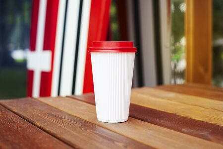 ripple: Ripple white paper cup to takeaway on wooden floor outside the cafe. Surfing boards stand behind at the background Stock Photo