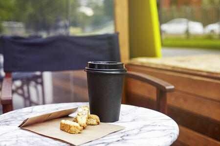 black paper disposable cup of coffee with cookies to take away on marble table in garden outside cafe. Breakfast morning on air Stock Photo