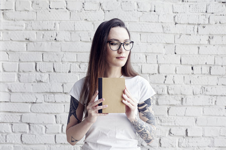Pretty hipster tattooed woman poses in white t-shirt with book in hands, isolated on white brick wall, Hold a book in hand, space for design layout