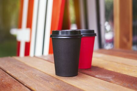Two red and black paper cups to takeaway on wooden floor outside the cafe. Surfing boards stand behind at the background