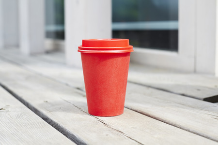 red paper cup of coffee to takeaway on wooden floor outside the cafe. Breakfast morning on air Stock Photo