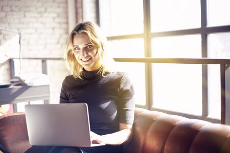 Beautiful blonde businesswoman sitting in sunny office working on laptop. Concept of young people working mobile devices. Sunshine throw windows on background Stock Photo
