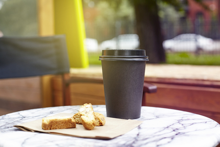 Back paper disposable cup of coffee with cookies to take away on marble table in garden outside cafe. Breakfast morning on air