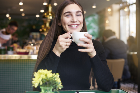 Young woman with long hair smiling, drinking cup of coffee in hands having rest in cafe near window