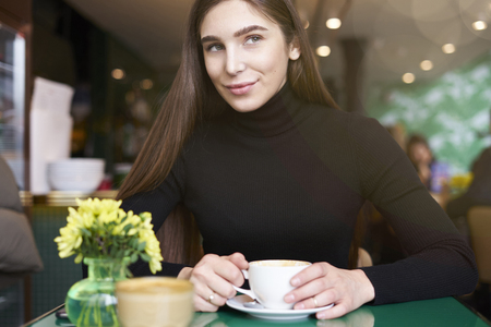 Young woman in black jersey look to camera, drink coffee and having rest in cafe near window