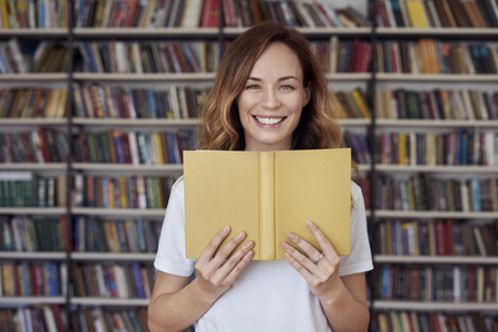 Portrait of smiling woman model with opened book in a library, bookshelf behind, long hair. Hipster college student lady.