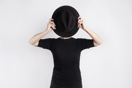 Woman in black hidden her face by black hat. Concept of metaphor, drama, hide emotion or personality