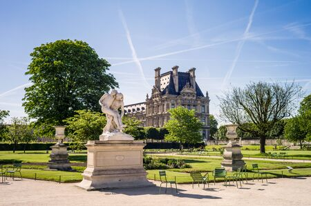 View of the Tuileries garden in Paris by a sunny morning with the statue of the Good Samaritan and carved vases in the foreground and the Flore pavilion of the Louvre palace in the background