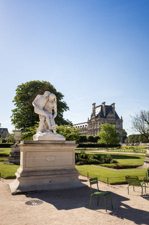 View of the Tuileries garden in Paris by a sunny morning with the statue of the Good Samaritan in the foreground and the Flore pavilion of the Louvre palace in the background Editorial