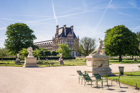 View of the Tuileries garden in Paris by a sunny morning with the statues of the Good Samaritan and Alexander Fighting in the foreground and the Flore pavilion of the Louvre palace in the background Editorial