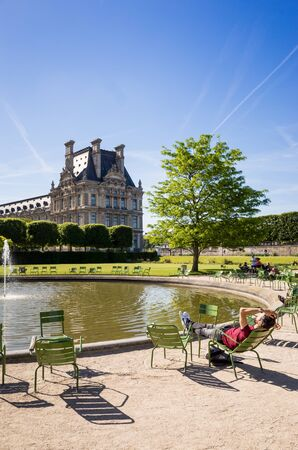 The Tuileries garden in Paris by a sunny morning with a man resting on a metal lawn chair near the Vivier Sud basin in the foreground and the Flore pavilion of the Louvre palace in the background Editorial