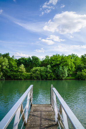 lonelyness: A wooden pontoon with metallic handrail over a river with trees and vegetation under a blue sky with white clouds.