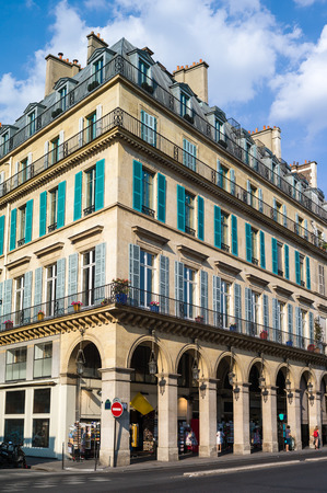 A typical Haussmannian building in Paris with balconies, shutters, arches and shops under a warm light of late afternoon.