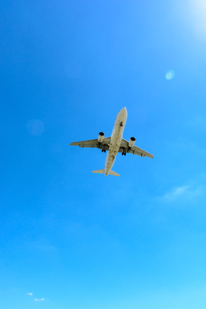 View from below of a flying airliner in landing approach or taking off.