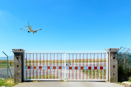 An airliner in landing approach flying above a closed fence gate with barbed wire.
