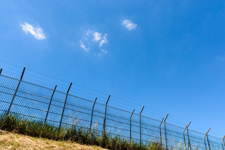 A border made of a double wire fence with barbed wire on top of a bank under a blazing sun and a summer blue sky.