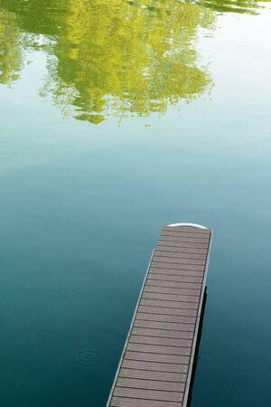 Narrow wooden pontoon over still green water.