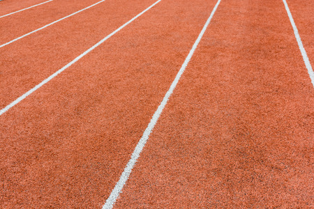 Close up view of a red athletics track with white lines defining the lanes.
